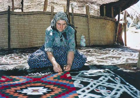 An Anatolian Turkmen woman from Karakoyunlu tribe seen sitting on the felt rugs she made in the black tent. Anamas Pasture, Beyşehir, Konya, 1980s