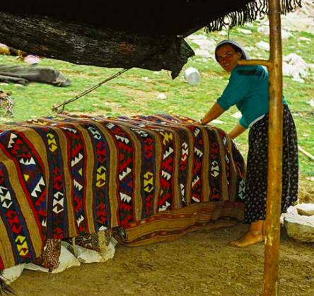 Sarıkeçili Turkmen tribeswoman showing the kilim she wove, covering the nomadic sacks in the tent. kdağ Pasture, Fethiye, South-Western Turkey, 180s, photo courtesy Josephine Powell, Suma Kıraç Foundation