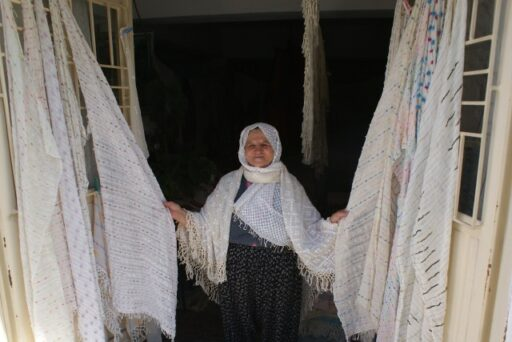 A weaver lady exposing the cotton fabrics that she wove, Üzümlü village, Fethiye, Southwestern Turkey, 2016